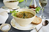 Green Lentil Coconut Soup in ceramic bowls served with bread and white wine