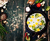 Pan of fried eggs on old green background