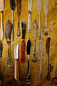 Verschiedene antike Buttermesser auf rustikalem Holzbrett