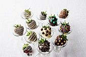 Variety of chocolate-covered strawberries in glasses