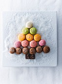 Macaroons and chocolate in shape of tree on plate with sugar