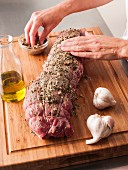 Hands rubbing garlic and pepper onto tenderloin