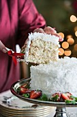 Hands serving slice of coconut cake