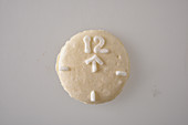 A white macaroon decorated to look like a clock with an arrow pointing to the 12