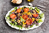 A salad platter with quinoa, chickpeas, yellow pepper, walnuts, red cabbage and blood orange