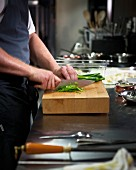 A chef chopping spring onions in a restaurant kitchen