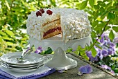 Cherry mascarpone cake on a cake stand in a garden