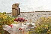 Sommerliche Beerentorte auf Holzbank am Strand