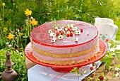 Erdbeer-Frischkäsetorte auf Tisch im Grünen