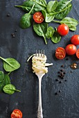 Linguine on a fork on a marble table, with tomatoes and spinach leaves