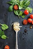 Linguine auf Gabel, daneben Tomaten und Spinatblätter