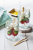 Tomato and mozzarella skewers with basil in glass jars