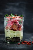Mixed leaf salad with avocado, tomato, radish, cabbage, goji and vegan mayo in a glass jar