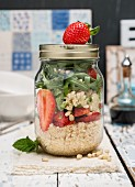 Vegan quinoa salad with strawberries and rocket in a jar