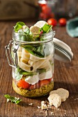 Italian pesto pasta vegetarian lunch jar in a rustic setting