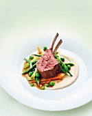 A rack of lamb with ginger jus, bean purée and spring vegetables