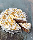 A carrot cake with carrots, apple, nuts and orange