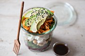 Spinatsalat mit Kichererbsen, Schafkäse, roter Bete und Avocado und Balsamico-Honig-Dressing im Glas