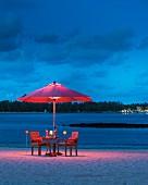 Romantische Abendstimmung an Sandstrand mit beleuchtetem Sonnenschirm und Armlehnstühlen