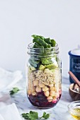 Layered salad with quinoa and vegetables in a glass jar