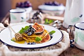 Gluten Free Pancakes With Figs And Blueberries with Mint on a white plate