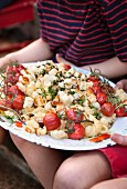 A pasta salad with grilled cherry tomatoes and halloumi on a serving platter