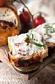 Fresh cheese with dried tomatoes and herbs on tomato bread