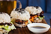 Sushi burgers with carrots, teriyaki meat, lettuce and black sesame