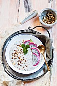 A smoothie bowl with yoghurt, chia seeds, dragon fruit and roasted hazelnuts