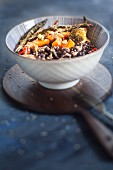 A vegan Buddha bowl with black rice, toasted vegetables and tahini sauce