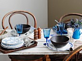 A table laid with blue glasses, blue and white plates and soup bowls