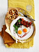 Grilled ham with fried eggs, peas, tomatoes and fries