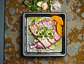 Marinated pork ribs with red onions, oranges and garlic