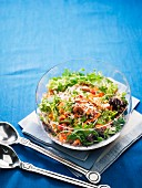 Rice salad with corn, rocket, carrots and cashew nuts in a glass bowl