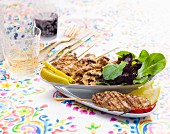 Grilled meat kebabs with a mixed leaf salad