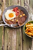 Steak in garlic sauce with a fried egg, ham and french fries