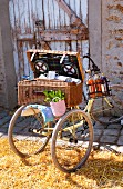 Picnic basket on tricycle on straw in front of barn