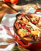 Chicken with bacon strips, tomatoes and tarragon in a casserole dish