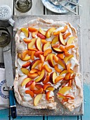 A summery meringue cake with cream, apricots and peaches