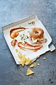 Bagel mit Ei auf Pizzakarton mit Essensresten