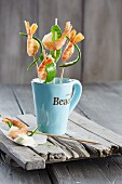 Prawn skewers with sugar snaps served in a mug