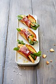 Parmesan tacos with melon, ham and arugula