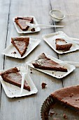 Sliced chocolate tart served on paper plates