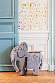 Alte Elefantenfigur vor einer Wand mit Kassettenverkleidung