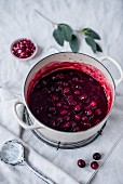 Hot cherries with cranberries and pomegranate seeds in a cooking pot