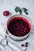 Heiße Kirschen mit Cranberries und Granatapfel im Kochtopf