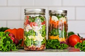 Two layered salads in glass jars with spinach, beans, cheese and eggs