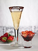 A champagne glass with chocolate and strawberries