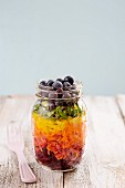 Rainbow salad in a glass with beetroot, carrots, yellow peppers, lettuce and blueberries