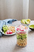Layered salad with quinoa, chickpeas, asparagus, radishes and sprouts